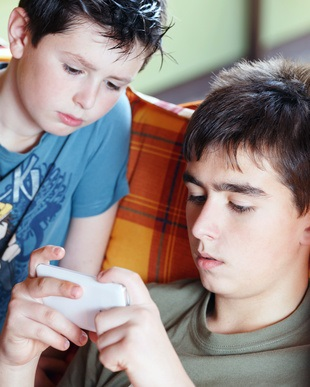 Handysucht: Teenager boys playing on smartphone, outdoor with shallow focus